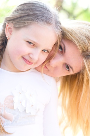 2 years old: Bright picture of hugging mother and daughter outdoors