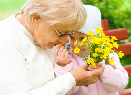Grandmother with granddaughter sniffing yellow flowers in the park Standard-Bild