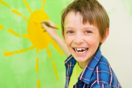 Chico lindo dibuja el sol en la pared en el hogar Foto de archivo - 19809349