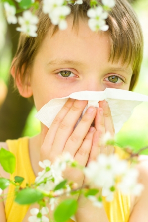 Little boy is blowing his nose outdoors photo
