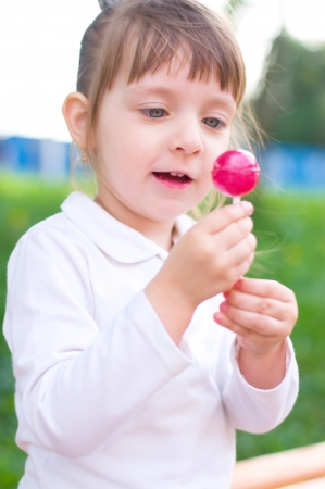 Happy little girl with lollipop outdoors photo