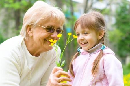 little girl giving her great grandmother yellow flowers Standard-Bild