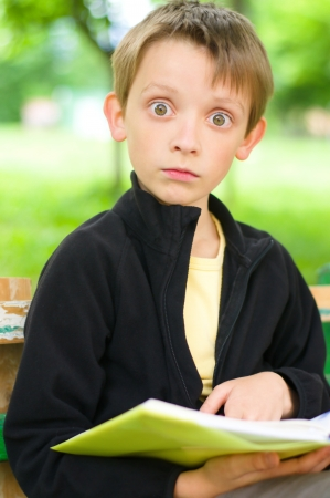 Young boy reading a book  at the park photo