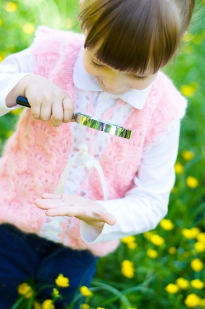 little girl is playing on green meadow examining hand using magnifying glass photo