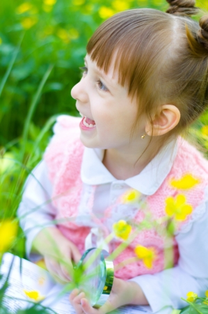 little girl is playing on green meadow examining field flowers using magnifying glass photo
