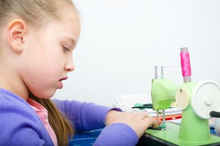 poco: linda chica de coser en una máquina de coser en su casa Foto de archivo