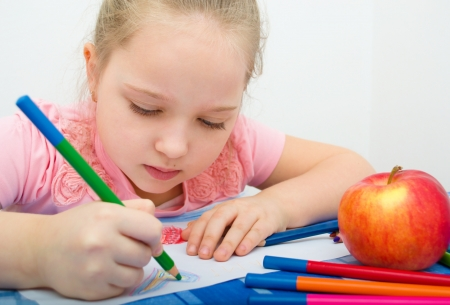 Closeup portrait of girl drawing with colorful pencil Standard-Bild