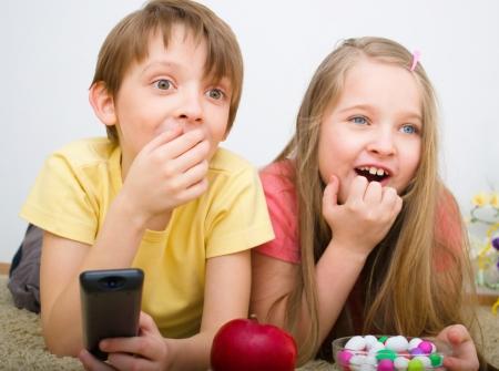 Children watching TV holding control Standard-Bild