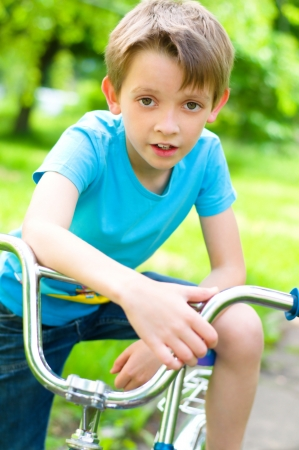 young boy riding bicycle in the summer photo