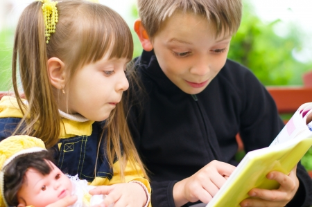 children reading the book at the park