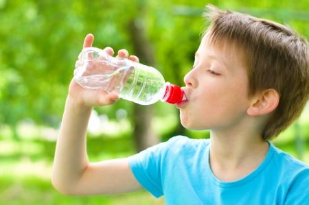 niño bebe agua de una botella al aire libre Foto de archivo