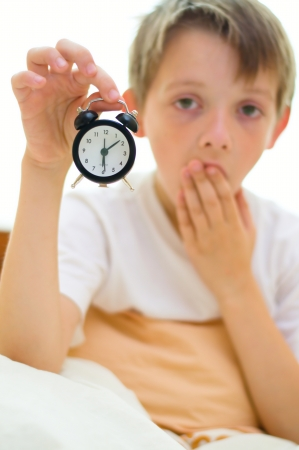 Little boy is holding clock while yawning photo
