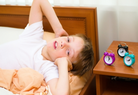 little boy with alarm clock on bed in the bedroom