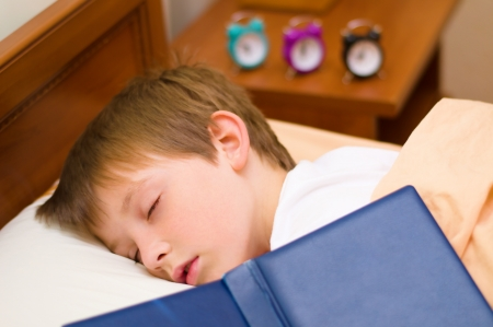 night school: Past bedtime for little schoolboy - asleep on his book Stock Photo