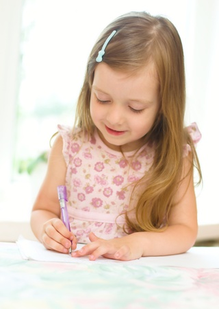 lectura y escritura: linda ni�a escribiendo algo en su cuaderno