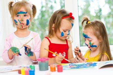 drie kleine meisjes tekenen met gouaches op papier