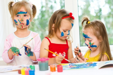 three little girls drawing with gouaches on paper Stock Photo - 20680125