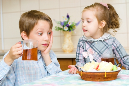 little girl with her brother sitting at the table drinking tea photo