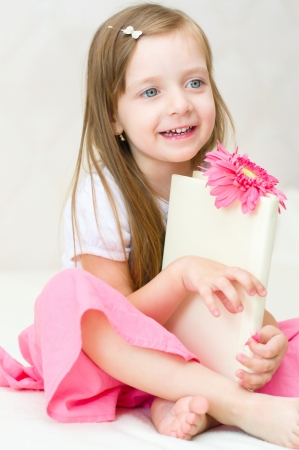happy little girl plays with book indoors photo