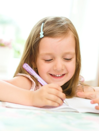 cute happy little girl writing something in her notebook photo
