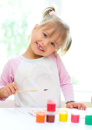 small girl: Cute little child painting with paintbrush and colorful paints