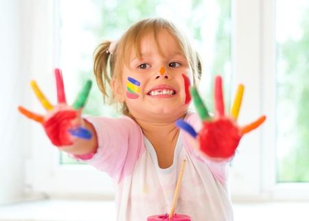 caritas pintadas: Niña linda con las manos pintadas en interiores