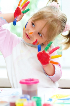 only baby girls: Cute little girl with painted hands indoors Stock Photo