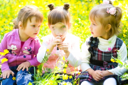 three little girls  playing on green meadow with magnifying glass