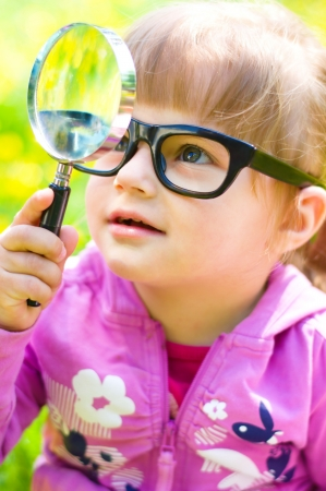 little girl is playing with magnifying glass on green meadow photo