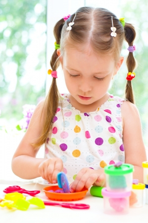 little dough: cute little girl is playing with  colorful play dough Stock Photo