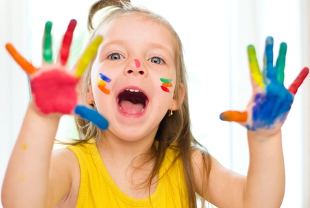 Cute little girl with painted hands indoors Фото со стока
