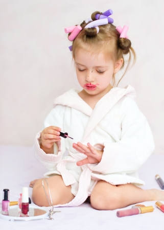 little girl painting nails while wearing hair-rollers, at home photo