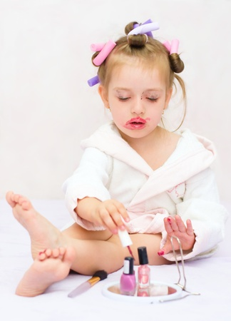 red bathrobe: little girl painting nails while wearing hair-rollers, at home