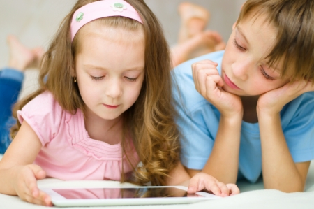 living room boy: little girl with her brother using tablet computer