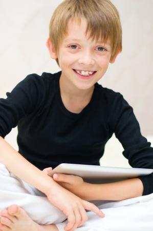 Happy little boy using tablet computer