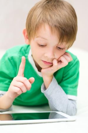 cute little boy using tablet computer