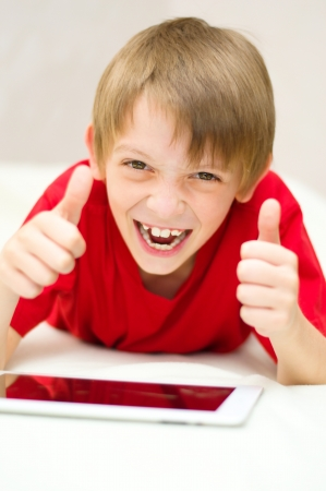 happy little boy using tablet computer photo