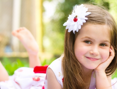 녹색 잔디에 누워 웃는 소녀의 초상화 스톡 콘텐츠