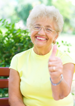 smiling elderly woman holding her thumb up outdoors photo