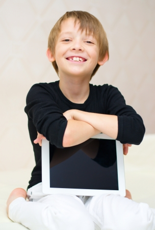 Happy little boy using tablet computer indoors photo