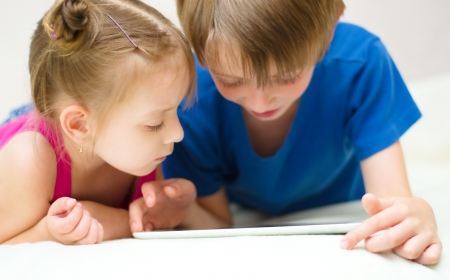 little girl with her brother using tablet computer at home