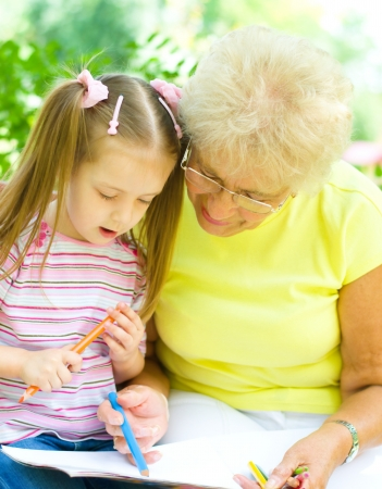 little girl with her grandmother drawing using crayons outdoors Stock Photo - 21512039