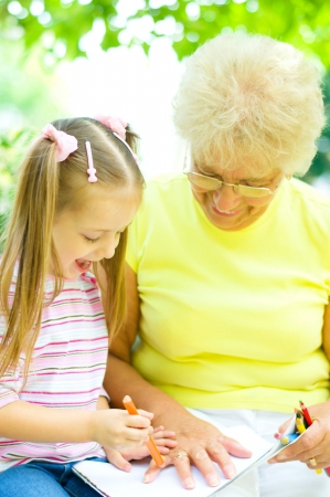 little girl with her grandmother drawing using crayons outdoors Stock Photo - 21512040