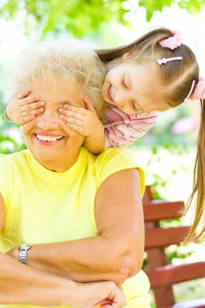 little girl plays with grandmother, closes her eyes outdoors Stock Photo