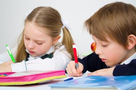 escuela primaria: Pequeños alumnos escriben en libro