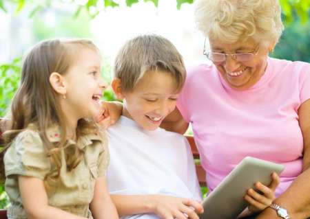 happy grandmother with grandchildren using tablet PC, outdoors photo