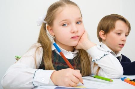 Little schoolgirl writing at school in workbook photo