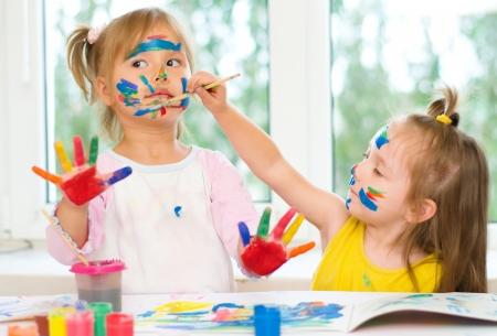 Dos niñas pintar con pincel y pinturas de colores Foto de archivo - 21767666