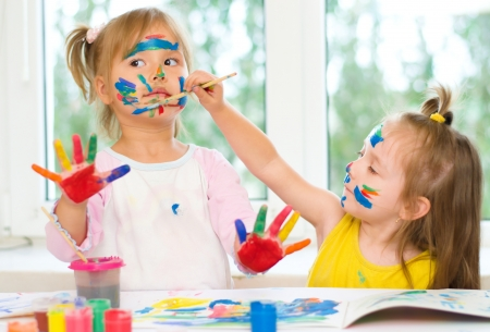 two little girls painting with paintbrush and colorful paints photo