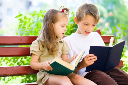 Portrait of cute kids sitting in the park and reading interesting book